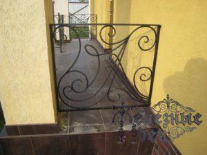Кованое ограждение между стеной дома и колонной на крыльце